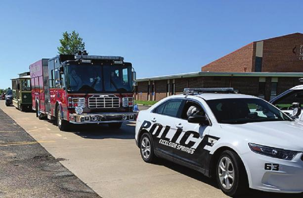 A POLICE CRUISER, a fire truck and the chamber trolley park at First United Methodist Church before the parade.