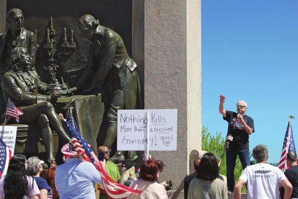 "RADIO SHOW HOST Dave ""Super Dave"" Day warms up the Reopen Missouri crowd of about 500 people at the ""Signing of the Treaty"" sculpture on the Capitol grounds Tuesday in Jefferson City. Several crowd members carry signs that denounce Gov. Mike Parson for issuing a stay-home order."