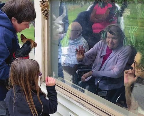 AT A WINDOW at the Valley Manor Nursing & Rehabilitation Center, visitors and their dog offer comfort to facility residents during the Valley Manor pet parade.