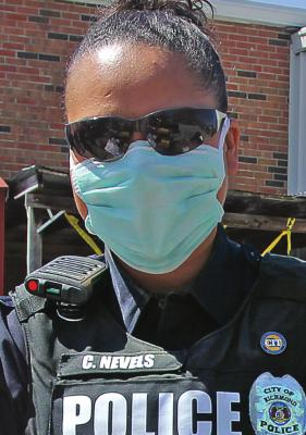 FIRST RESPONDERS RECEIVE FAULTY MASKS RICHMOND Police Officer Chassity Nevels wears a facemask to give out commodities. Masks are expected to help keep wearers from transmitting or being infected by COVID-19, but the state sent emergency management agencies faulty masks. J.C. VENTIMIGLIA | Staff