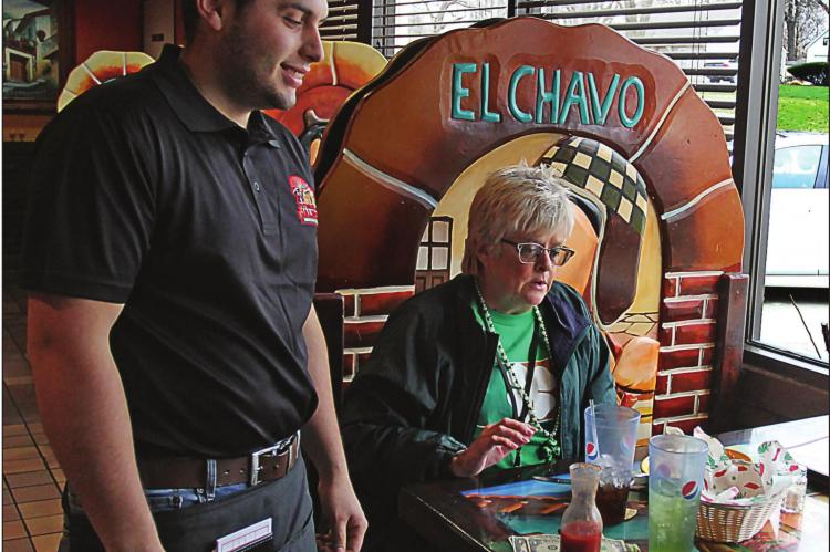 AT TEQUILA JALISCO Mexican Restaurant in Richmond, the doors last week remain open and Heraldo Hacentio waits on a customer, Janis Kincaid, Excelsior Springs. On Tuesday, the commission ordered restaurants to close their doors to walk-in customers.