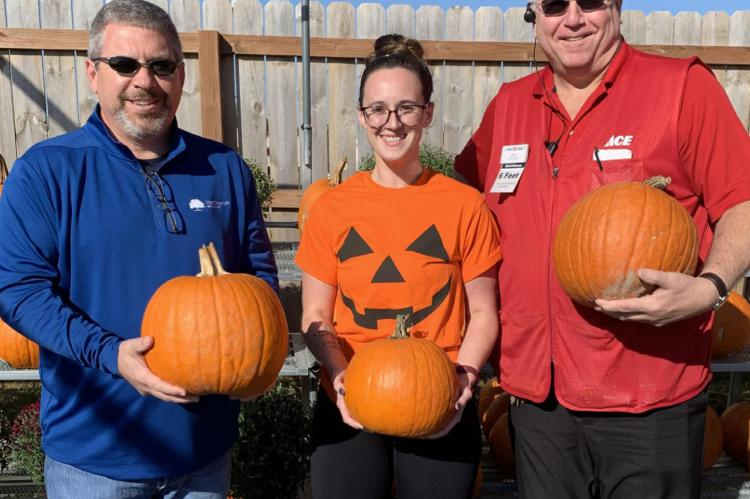 PUMPKINS READY: From left are Tray Harkins with the Gregg Williams Foundation and Flat Branch Home Loans; Cassie Kinnard, Excelsior Springs Community Center aquatics manager; and Bill Westerheide, Westlake ACE Hardware of Excelsior Springs.