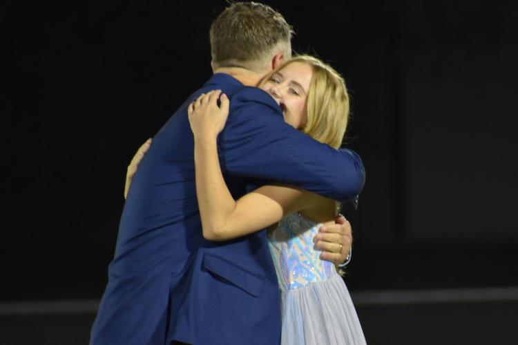 Emily Milledge shares a hug with her father after being announced queen. (Photo by Christi Rice)