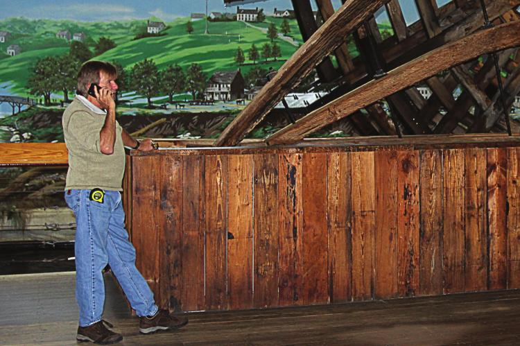 ALWAYS BUSY, one of the people who excavated the Arabia, David Hawley, talks on the phone while standing beside the steamboat's recreated paddlewheel, which uses some original parts from the paddlewheel taken out of the Missouri River in 1988.