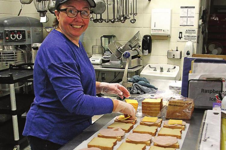 SANDWICHES are made with care and efficiency by cafeteria worker Debra Doss.