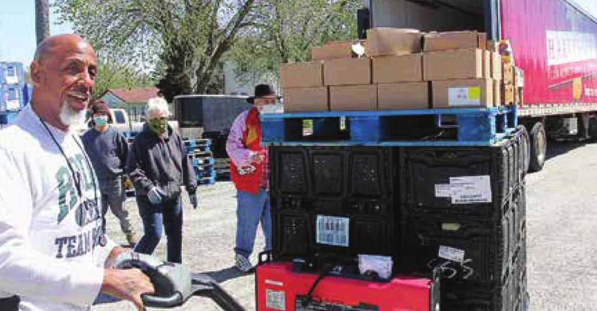 A DRIVER for the Harvesters Community Food Network in Kansas City, Frank Gray, unloads food from the trailer onto the lot of the Salvation Army Family Store in Richmond.
