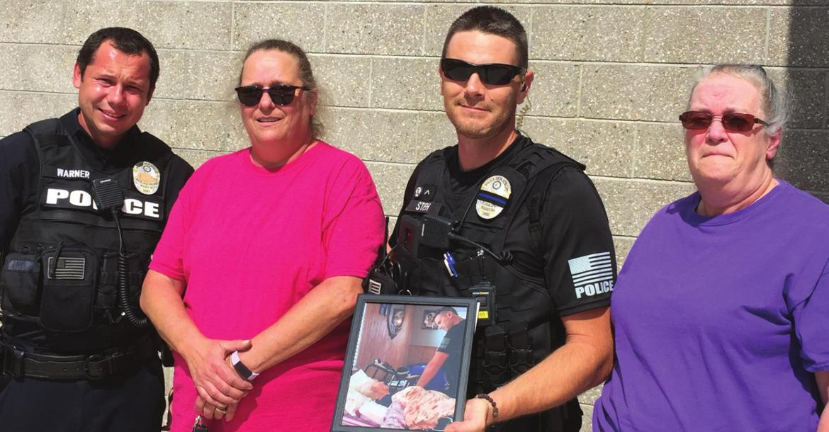 SISTERS Gail Vassmer and Julane Hicks show appreciation for the Excelsior Springs Police Department. From left are Officer Robert Warner, Vassmer, Officer Kenneth Stieh and Hicks. The sisters present Stieh with their thanks and a framed photo of Stieh and their mother, Madolyn Eberts, taken during one of Stieh's visits with Eberts in the hospital.