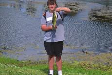 GRIFFIN SMITH shows off the bass he caught this week while fishing at Century Park in Excelsior Springs. Fishing is among the many outdoor activities area residents can enjoy this summer in Excelsior Springs. DUSTIN DANNER | Staff