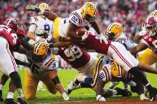 IT TAKES FOREVER for the Kansas City Chiefs to draft Clyde Edwards-Helaire, seen leaping through the University of Alabama defense for LSU. COURTESY OF THE LSU ATHLETICS WEBSITE